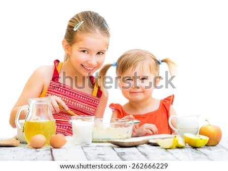 two smiling little sisters cooking and looking into the camera isolated on a white background - stock photo