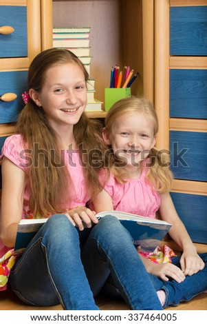 two smiling little sisters reading at their room - stock photo