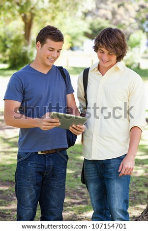 Two smiling male students with a touch pad in a park - stock photo