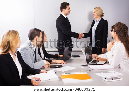Two smiling managers handshaking and celebrating advantageous deal - stock photo