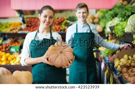 Two smiling market workers offering for retail large squash