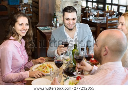 Two smiling  married couple sitting at restaurant table - stock photo