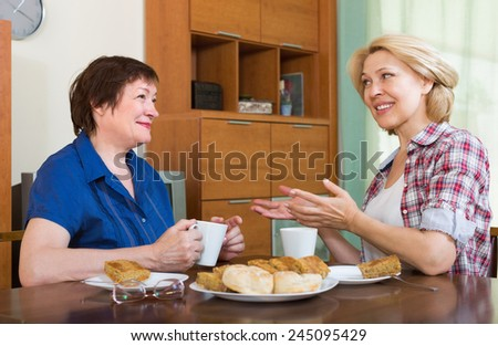 Two smiling mature female drinking tea and gossiping at table - stock photo