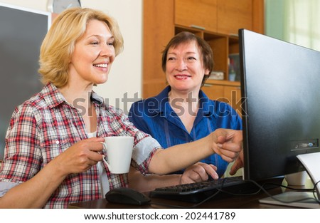 Two smiling mature female friends drinking coffee and browsing web - stock photo