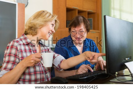 Two smiling mature women friends drinking tea and browsing web - stock photo