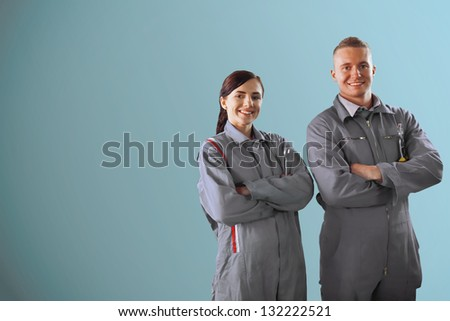 Two smiling mechanics standing on a blue background