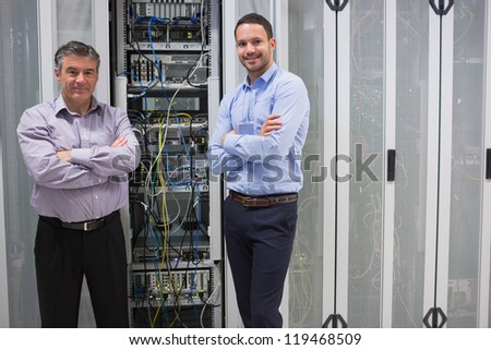 Two smiling men standing in front of servers in data center - stock photo