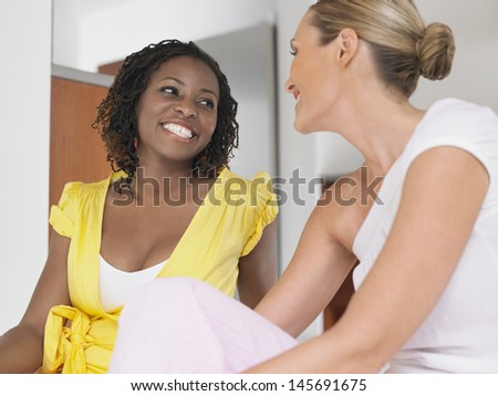 Two smiling multiethnic women conversing indoors - stock photo