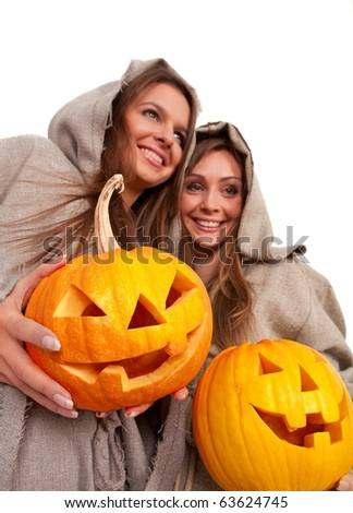 Two smiling nuns in cassocks holding halloween pumpkins over white - stock photo
