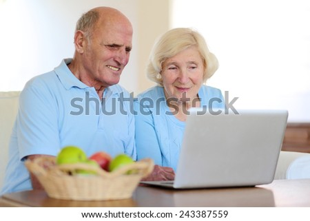 Two smiling people, active senior couple, eating fruits and enjoying modern technology using laptop computer with wireless internet at home - stock photo