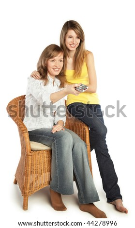 Two smiling pretty blond girls watch TV; isolated on white background - stock photo