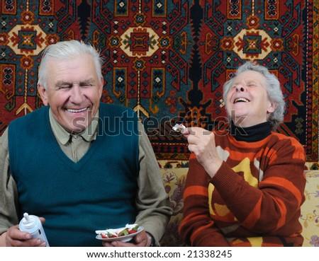 two smiling senior eating dessert - stock photo