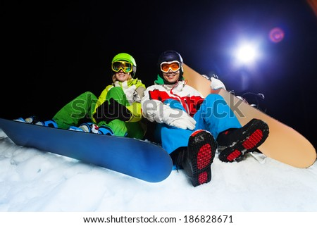 Two smiling snowboarders sitting at night - stock photo