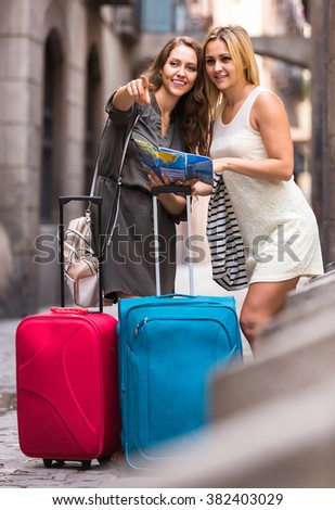 Two smiling spanish women with baggage checking route outdoors - stock photo