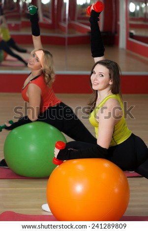 Two smiling sporty girls do exercises for arms on colorful pilates balls
