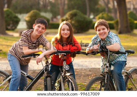 Two smiling teenage boys and one teenage girl having fun on bicycles in the park. - stock photo