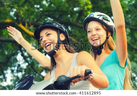 Two smiling teenage girlfriends riding scooter on sunny summer day.