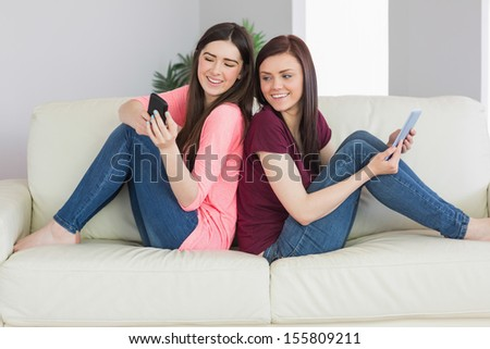 Two smiling teenage girls sitting back to back on a sofa using a tablet pc and a mobile phone