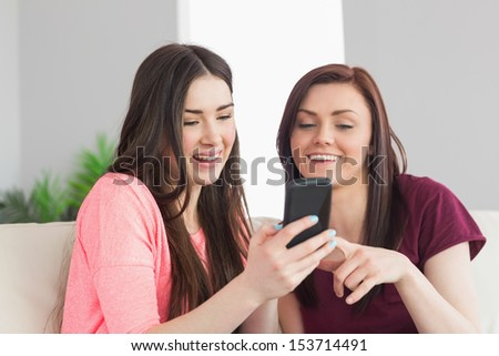 Two smiling teenage girls sitting on a sofa laughing and using a mobile phone in a living room