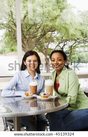 Two smiling woman sitting enjoying muffins and coffee drinks at a cafe. Vertical shot. - stock photo