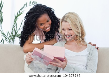 Two smiling women are looking inside a pink box at a present - stock photo