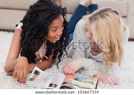Two smiling women are lying on the floor and talking with a magazine in front of them
