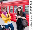Two smiling women are near the train - stock photo