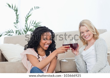 Two smiling women are sitting on the floor holding wine glasses - stock photo