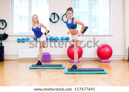 Two smiling women do stretching exercise in sports club. Fitness gym