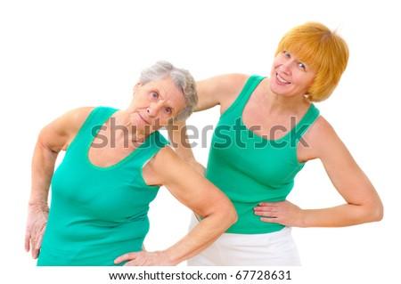 two smiling women doing gymnastics on white background - stock photo
