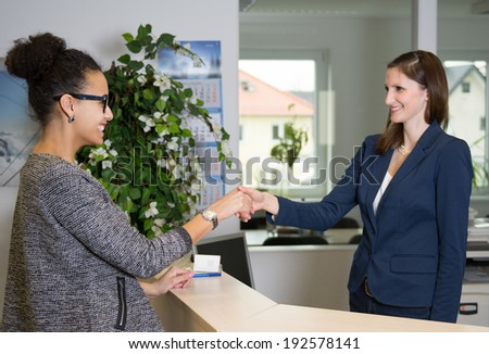 Two smiling women greet each other with handshake over a counter in the office. - stock photo