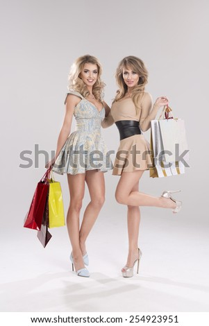 Two smiling women holding bags  - stock photo