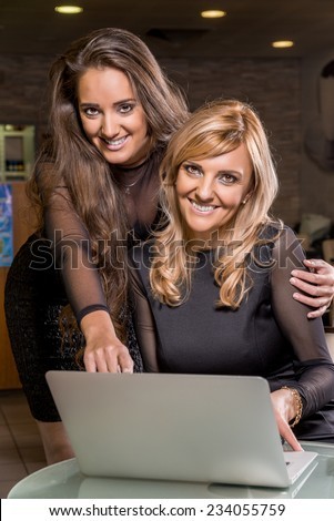 Two smiling women looking a laptop and smiling. - stock photo