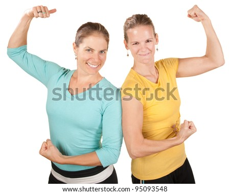 Two smiling women show off their biceps