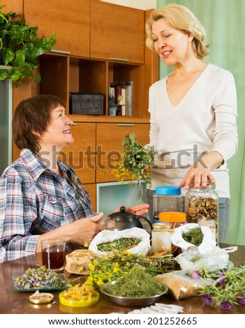 Two smiling women sitting at the table with herbal tea and herbs