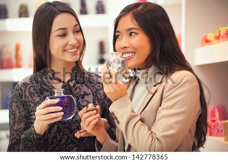 Two smiling women smelling the fragrance of different aromatherapy oils.
