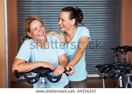 Two smiling women standing in room in a gym - stock photo