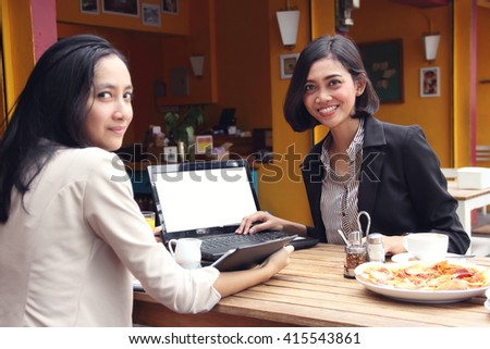 Two smiling young Asian business women hanging out in an old restaurant