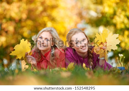 Two Smiling young attractive women with autumn maple leaves in park at fall outdoors - stock photo