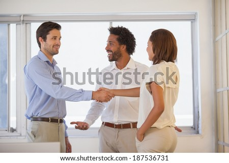 Two smiling young business people shaking hands besides colleague at the office - stock photo