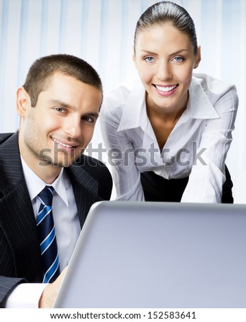 Two smiling young businesspeople working with laptop at office - stock photo