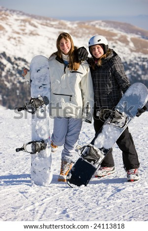 Two smiling young girls on snowboard - stock photo