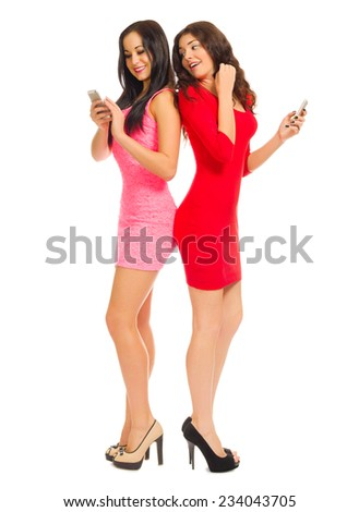 Two smiling young girls with mobile phones isolated - stock photo