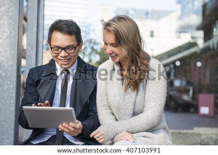 Two smiling young people looking into digital tablet sitting outside on city street
