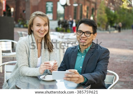 Two smiling young people with mobile device while sitting at outdoor cafe table on city street - stock photo