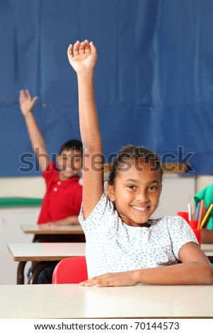 Two smiling young school children arms raised in class - stock photo