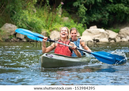 Two smiling young women kayaking down a river - stock photo