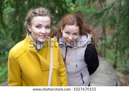 Two smiling young women standing together and looking at camera in park