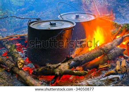two smoke tourist kettle on fire - stock photo