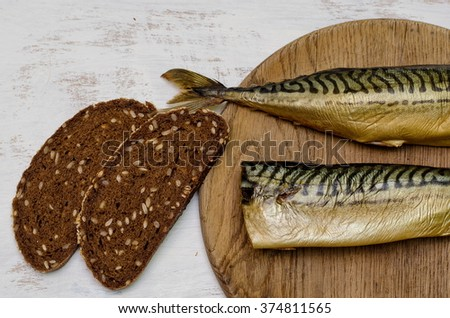 Two smoked mackerels with rye bread on white painted background  - stock photo